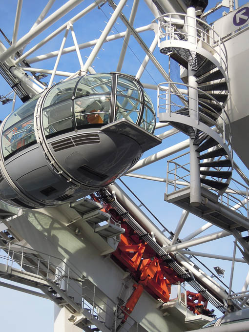 Photograph, detail, daytime: a London Eye capsule passing a static structure and metal spiral staircase, as it completes the circuit back to land