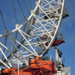 "Photograph, close, daytime: detail of the London Eye orange machinery including the red ""key"" capsule"