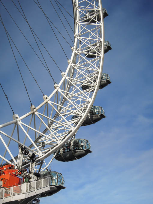 Photographed from below, daytime: a section of the London Eye including several capsules and orange machinery